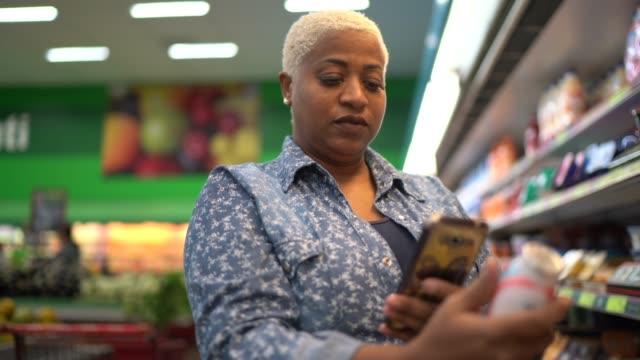 vídeos de stock, filmes e b-roll de mulher compra em supermercado usando celular - liquidação evento comercial