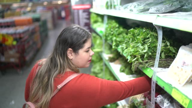 Woman buying at supermarket Woman buying at supermarket fat nutrient stock videos & royalty-free footage