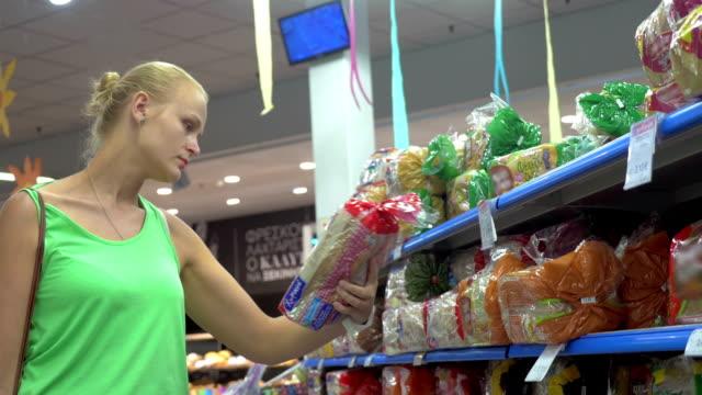 여자 구매 식빵 있는 슈퍼마켓 - 식빵 한 덩어리 스톡 비디오 및 b-롤 화면