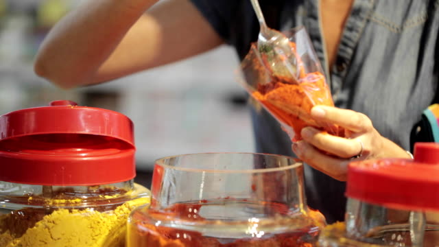 Woman buying cinnamon, paprika and curry powders in organic supermarket video