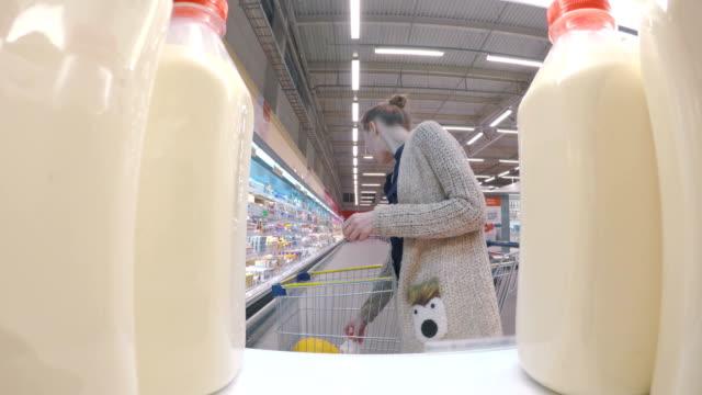 vídeos y material grabado en eventos de stock de mujer comprar leche fresca en el supermercado - leche