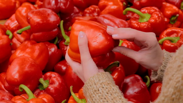 Woman buying fresh red bell peppers at grocery store Woman buying vegetables - fresh red bell peppers at supermarket. Close up shot of woman hands. Consumerism, sale, organic and health care concept paprika stock videos & royalty-free footage