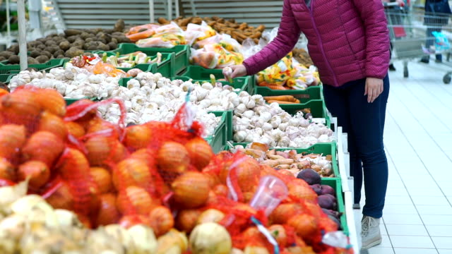 woman buying garlic on the food grocery store - aglio alliacee video stock e b–roll