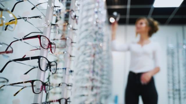 Bидео Woman buying new glasses