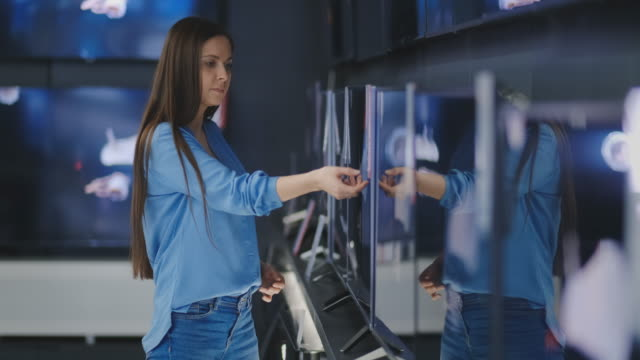 Woman buying TV in a store. 4K UHD