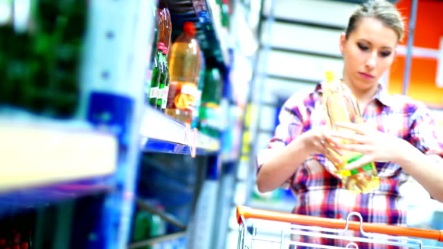 frau kauf wasser im supermarkt. - alkoholfreies getränk stock-videos und b-roll-filmmaterial
