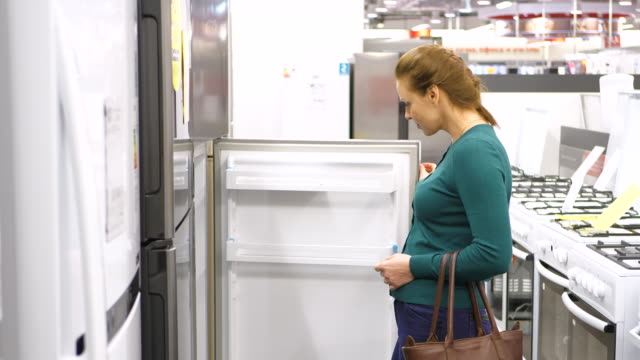 woman buys a refrigerator in store. 4k UHD. woman buys a refrigerator appliance stock videos & royalty-free footage
