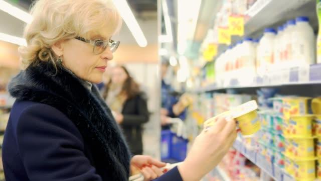 frau kauft joghurt im store - etikett stock-videos und b-roll-filmmaterial