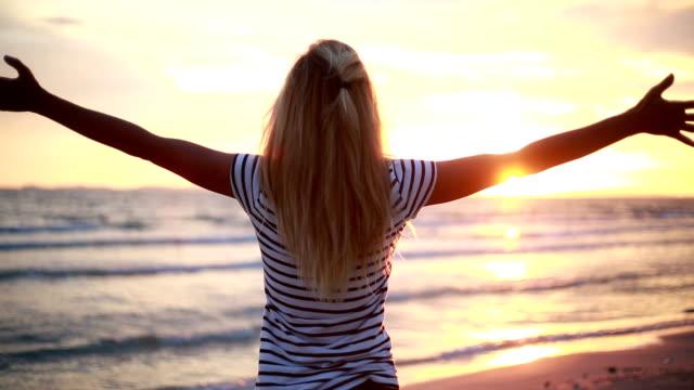 vídeos y material grabado en eventos de stock de mujer en la playa al atardecer, brazos estirados - miembro humano