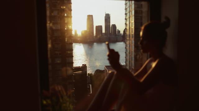 donna vicino alla finestra a new york - calore concetto video stock e b–roll