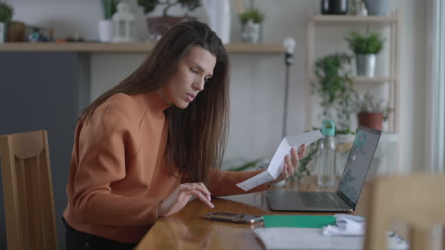 Woman calculating and handling paperworks and going through her financial bills at home Young beautiful woman calculating and handling paperworks and going through her financial bills at home financial planning stock videos & royalty-free footage