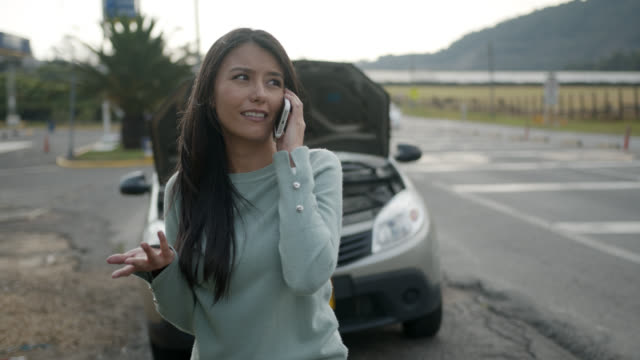 Woman calling for roadside assistance as her car broke down
