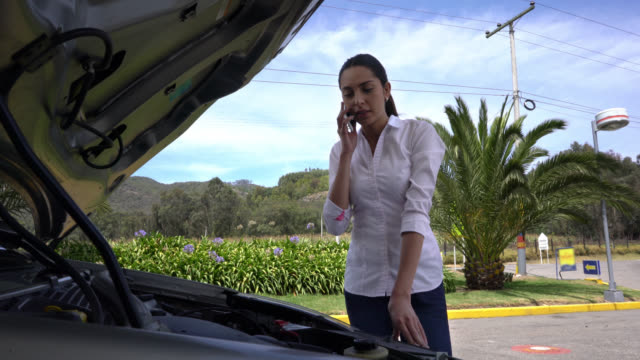 Woman calling for vehicle assistance for her car video