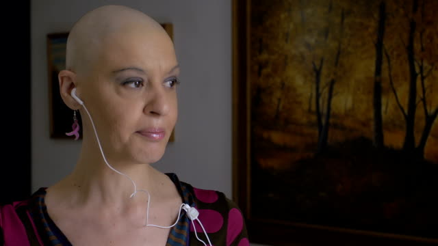 woman cancer survivor speaking at mobile phone: chemotherapy, bald, video