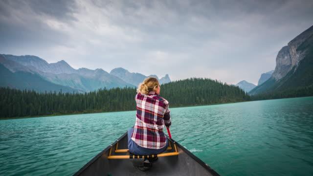 vídeos de stock, filmes e b-roll de canoagem no lago imaculado de mulher - remo esporte aquático