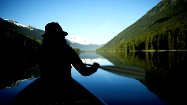 woman canoeing on a pristine lake - canada travel stock videos and b-roll footage