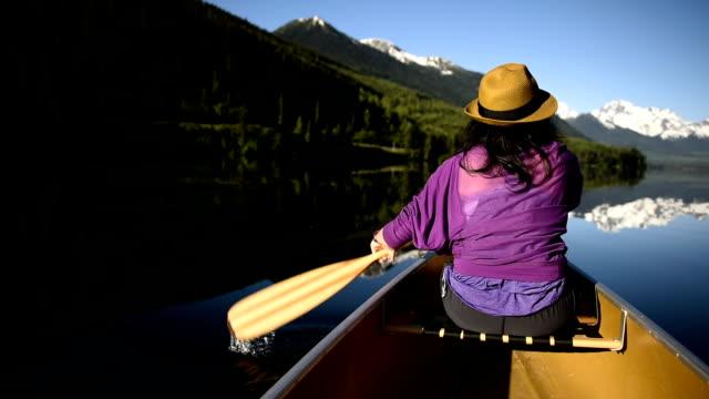 Woman canoeing on a pristine mountain lake video