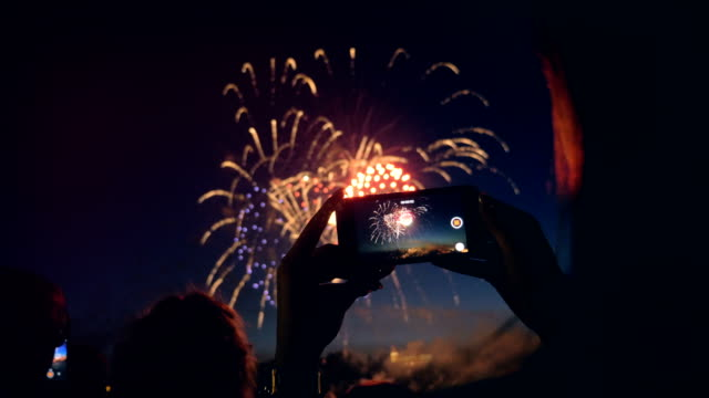 A woman captures fireworks on video, close up. One person uses a phone to film the fireworks. bastille day stock videos & royalty-free footage