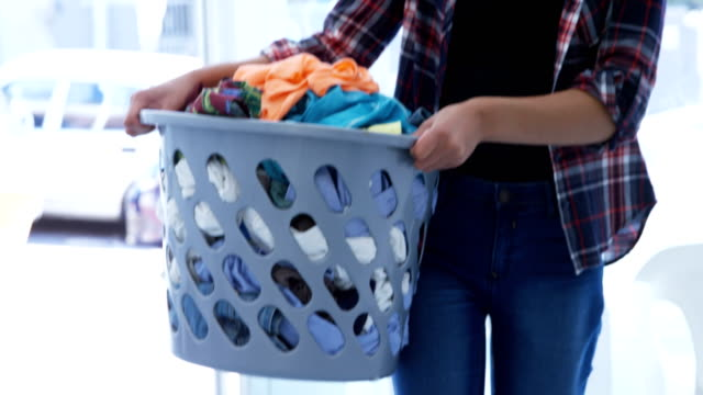 Woman carrying clothes in laundry basket at laundromat 4k Mid section of woman carrying clothes in laundry basket at laundromat 4k laundry basket stock videos & royalty-free footage