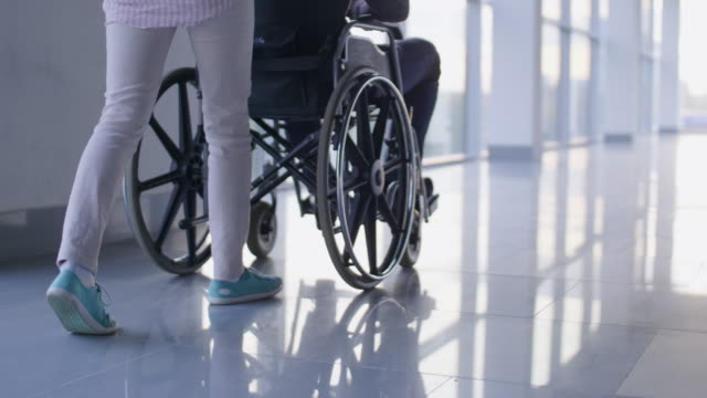 Woman carrying invalid in wheelchair Low-section shotof nurse pushing driving wheelchair with handicapped patient through the corridor with mirror floor pushing wheelchair stock videos & royalty-free footage