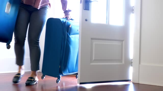 woman carrying luggage into home ar front door. - arrivo video stock e b–roll