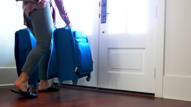 stockvideo's en b-roll-footage met vrouw met bagage uit voordeur thuis. - ingepakt