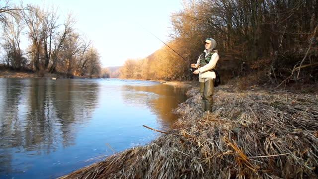 川岸に立っている間に、ある女性が紡績魚を捕まえる - 漁師 外人点の映像素材/bロール