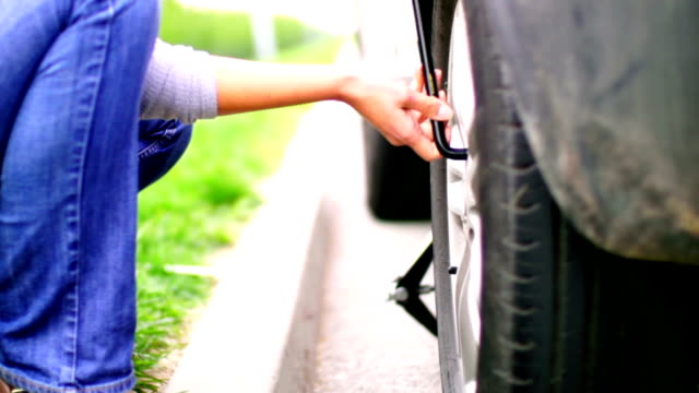 Woman changing flat tire on her car. video