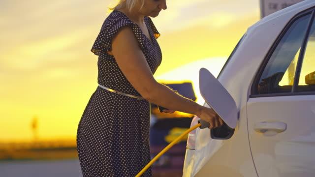 SLO MO Woman charging a car at the charging station at sunset
