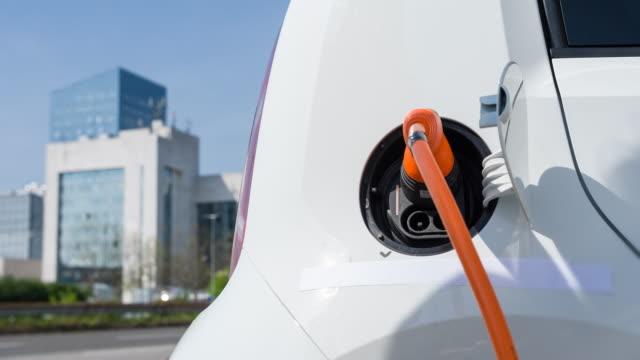 女性環境フレンドリーな代替エネルギー燃料車を充電 - 電気自動車点の映像素材/bロール