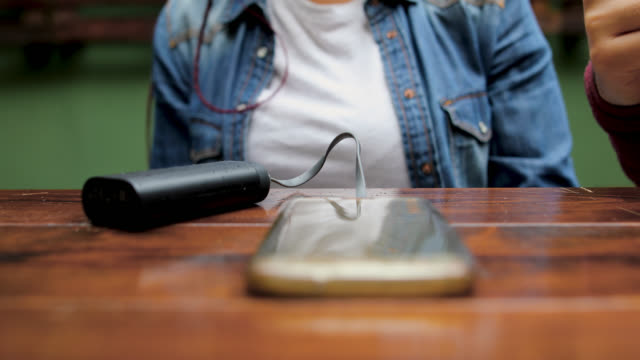 kadın kafede otururken powerbank pil şarj cihazı ile akıllı telefon şarj - taşınabilirlik stok videoları ve detay görüntü çekimi