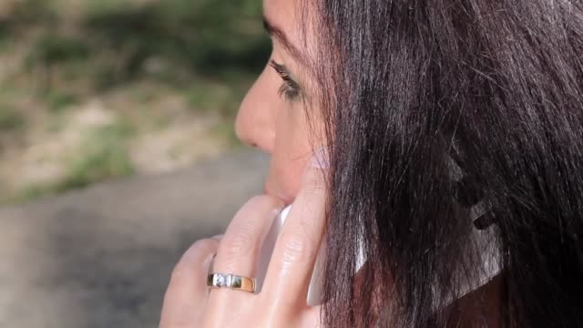 Woman chating with a friend Footage of a mature woman talking on the phone in a park. donna stock videos & royalty-free footage
