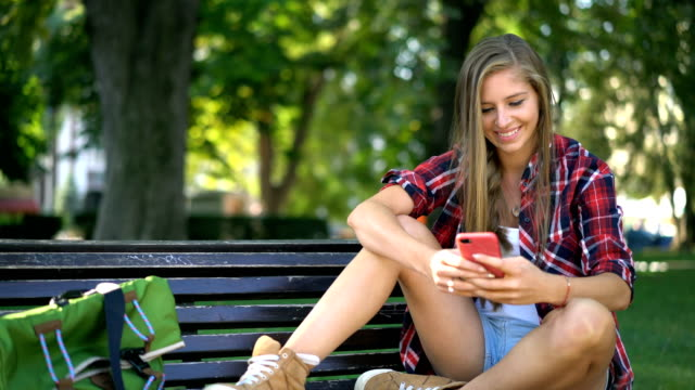 公園で彼女の携帯電話でのオンライン チャットの女性 - ベンチ点の映像素材/bロール