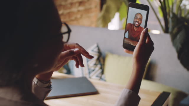 Woman Chatting with Afro-American Male Friend on Video Call in Cafe