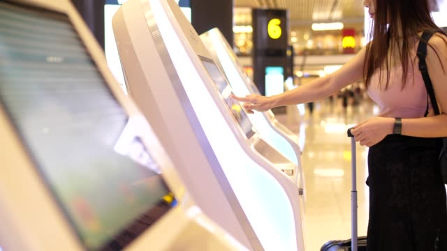 frau checkt flug von kiosk-maschine ab - smart city stock-videos und b-roll-filmmaterial