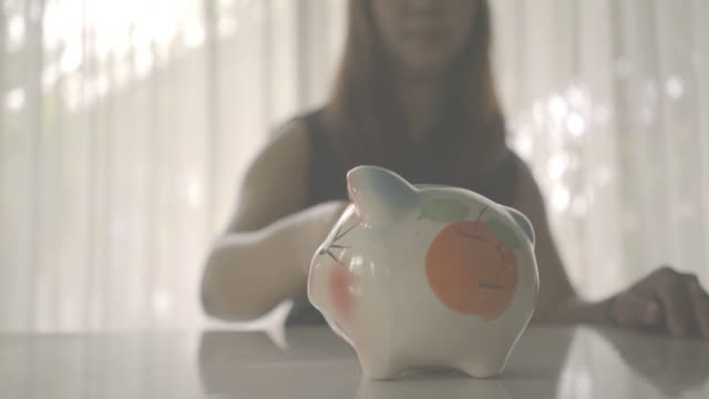 woman checking a coin in piggy bank - savings stock videos & royalty-free footage