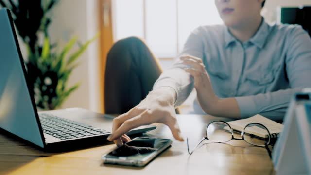 vidéos et rushes de femme de ds vérifiant un téléphone mobile tout en travaillant sur un ordinateur portatif de la maison - 20 24 ans