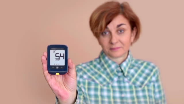 Woman checking and showing glucose meter after measuring blood sugar video
