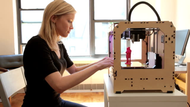 Woman checking print on open source 3D printer video