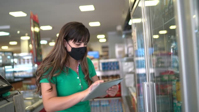 フェイスマスク付きデジタルタブレットを使用してパン屋やスーパーマーケットで製品をチェックする女性 - コントロール点の映像素材/bロール
