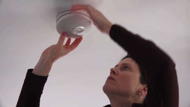 stockvideo's en b-roll-footage met vrouw die rookalarm controleert - alarm, home,