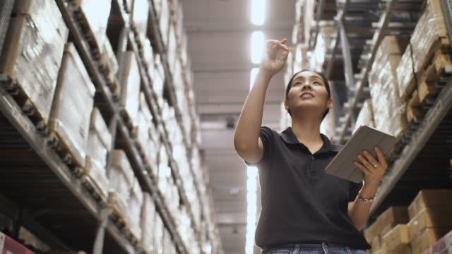 女性の倉庫でチェック用品 - 貨物運送点の映像素材/bロール