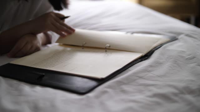 女性がベッドの上の作業フォルダーをチェック - テーブル 無人のビデオ点の映像素材/bロール