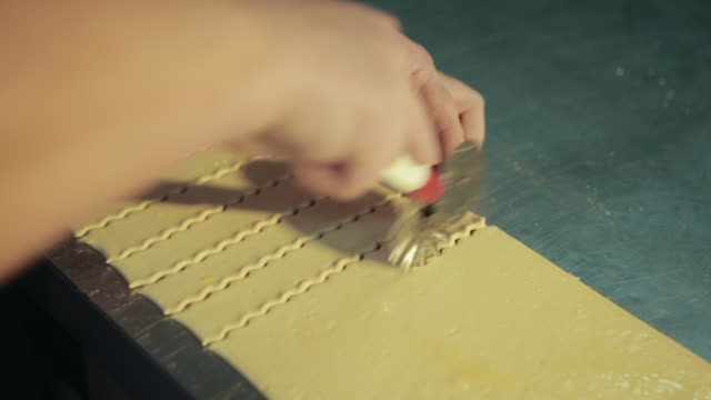 Woman chef uses roller knife or pastry wheel to cut, make curved edge.