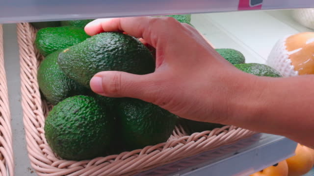 Woman Choose Avocados In Supermarket Shot By Smart Phone
