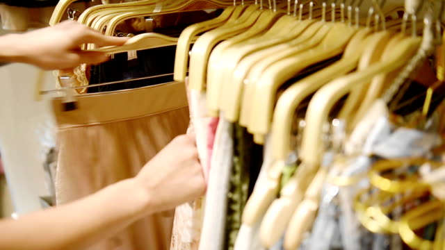 A Woman Chooses A Dress In A Clothing Retail Store. Close Up Hands. A Woman Chooses A Dress In A Clothing Retail Store. Close Up Hands. dress stock videos & royalty-free footage