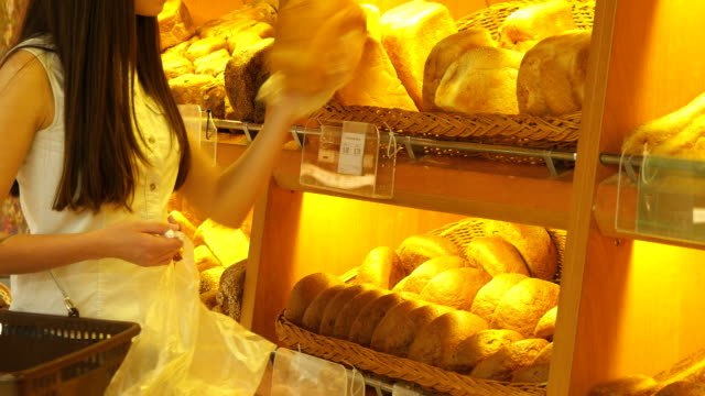 Woman chooses and putting a fresh bread loaf into a package in the supermarket. Young girl taking a loaf of bread from the shelf and putting it into the basket. Shopping in the grocery