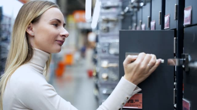Woman chooses door handles in the store Woman chooses door handles in the store. handle stock videos & royalty-free footage