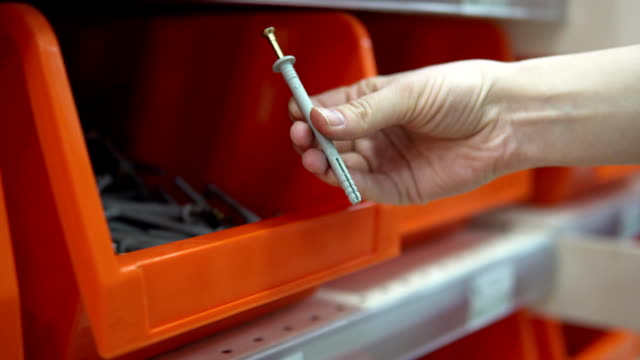 A woman chooses dowel-nail in a store of construction goods. Close-up of a hand takes an orange container from a dowel-nail. Selection and purchase of building materials in the hypermarket. bolt fastener stock videos & royalty-free footage
