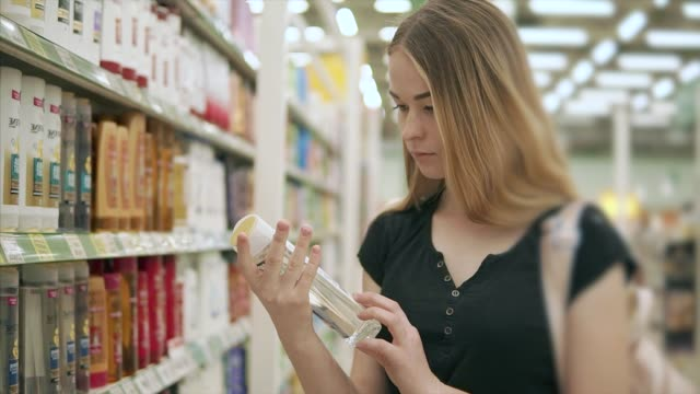 woman chooses new shampoo. - igiene video stock e b–roll